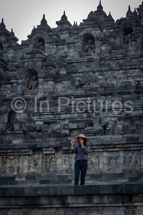 An Indonesian woman wearing a red wide brimmed hat takes selfies in front of Borobudur Temple on the 24th October 2019 in Java in Indonesia. Borobudur is a 9th-century Mahayana Buddhist temple in Magelang Regency. It's the worlds largest Buddhist temple, consisting of nine stacked platforms, six square and three circular, topped by a central dome.