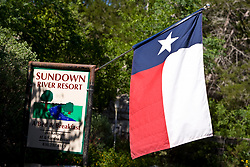 Stock photo of a Texas flag hanging at the entrance of a local bed and breakfast in the Texas Hill Country