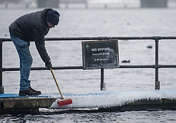 © Licensed to London News Pictures. 03/03/2018. London, UK. A man attempts to remove ice from a diving board before members of the Serpentine Swimming Club brave freezing overnight temperatures to enjoy an early morning dip at sunrise in the Serpentine in Hyde Park, London. Large parts of the UK are recovering from a week of sub zero temperatures and heavy snowfall, following two severe cold fronts. Photo credit: Ben Cawthra/LNP