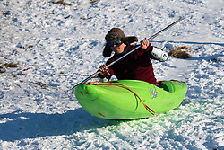 Man in kayak slides down snow covered hill in Holyrood Park, Edinburgh, Scotland, UK