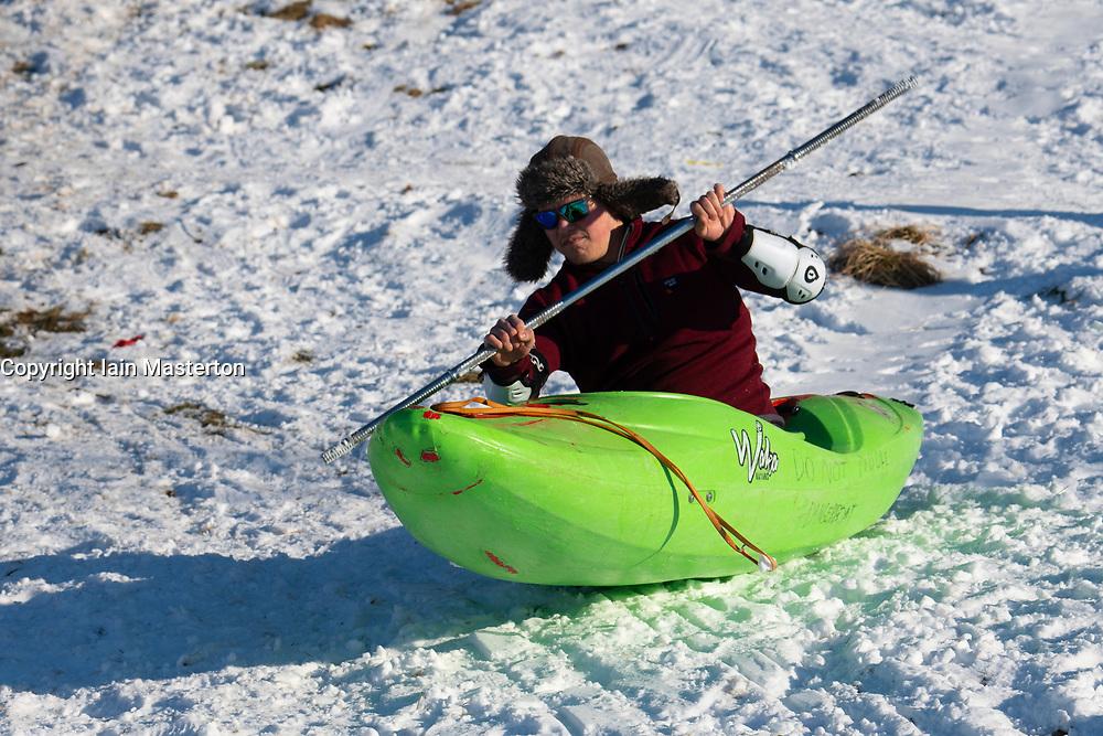 Man in kayak slides down snow covered hill in Holyrood Park, Edinburgh, Scotland, UK