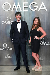 Professor Brian Cox and partner Gia Milinovich attending the Lost in Space event to celebrate the 60th anniversary of the OMEGA Speedmaster held in the Turbine Hall, Tate Modern, 25 Sumner Street, Bankside, London.
