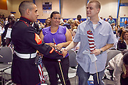 """04 JULY 2009 -- PHOENIX, AZ:  Sgt. DAVID CASTILLO, US Marine Corps, and new US citizen originally from Venezuela, greets other new citizens at a naturalization ceremony in Phoenix, July 4. U.S. Citizenship and Immigration Services and South Mountain Community College in Phoenix, AZ, hosted the 21st annual """"Fiesta of Independence"""" Saturday, July 4. More than 180 people from 58 countries took the US Oath of Citizenship and became naturalized US citizens. The ceremony was one of dozens of similar ceremonies held across the US this week. USCIS said more than 6,000 people were naturalized US citizens during the week.  Photo by Jack Kurtz / ZUMA Press"""