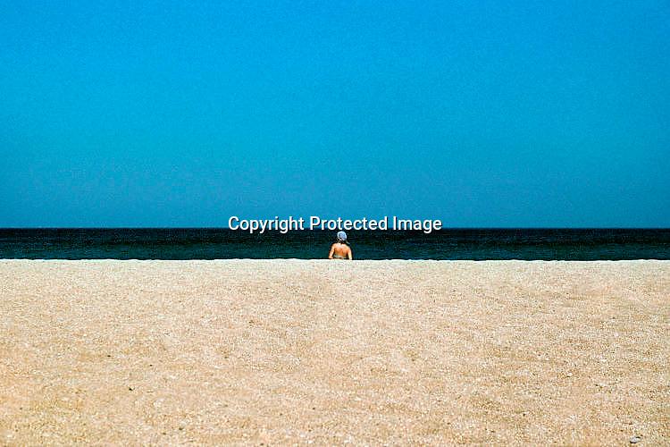 Griekenland, Kreta, 2-6-2005Zon, zee en zand. Strand met vrouw in bikini op het oostelijke deel van het eiland. vakantie, vakantieeiland, vakantiebestemming, blauwe lucht. Rust, uitrusten, ontspannen, bijkomen van stress, hectiek van werk, werkdruk, jachtig leven.Foto: Flip Franssen/Hollandse Hoogte