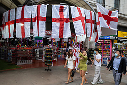 © Licensed to London News Pictures. 10/07/2021. LONDON, UK.  England flags are offered for sale to revellers and passers by in Piccadilly Circus ahead of the final of Euro 2020 between Italy and England tomorrow night Wembley Stadium.  It is the first major final that England will have played in since winning the World Cup in 1966 but Italy remain unbeaten in their last 33 matches.  Photo credit: Stephen Chung/LNP