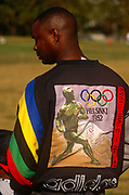In the run-up to the forthcoming Olympics in Atlanta, a young black man displays a vintage design for the '52 Helsinki games. With the corporate sports label Adidas along the bottom of the top, the man stands on a sports field near this American Downtown city that hosted its own games in 1996. Showing a running athlete from the ancient Greek era and the five Olympic rings owned by the IOC.