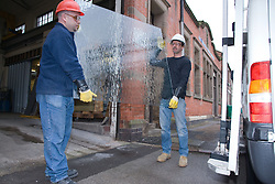 Two glazier lifting a pane of glass towards their van,