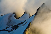 Low clouds envelope the sharp summit ridges Eldorado Peak at sunset, North Cascades National Park, Washington.