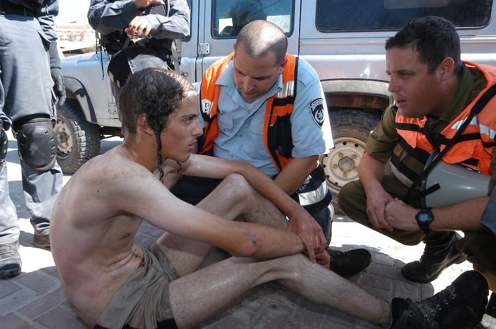 Paramedic and IDF officer checking a young Jewish settler condition after being evacuated from the home made bunker after spending there the whole night and morning.<br /> Settlers know that the evacuation would not declare complete until their bunker will be breech. the bunker was breech, in consideration of settlers life's and well being, three hours after the rest of the evacuation was done.<br /> The evacuation took place after a few Jewish settlers family took over houses outside of their permitted area in Hevron. The Supreme court order them to evacuate by will. once deadline for evacuation arrived, a green light was ordered for the force evacuation. <br /> Hevron, Israel.
