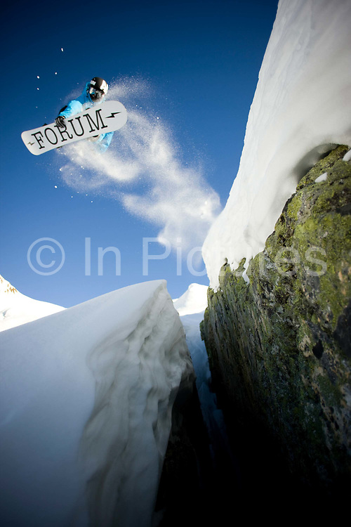 A male snowboarder jumps over a deep crevasse on the 24th January 2011 in La Plagne in France. La Plagne is a French ski area in the alpine valley of the Tarentaise.