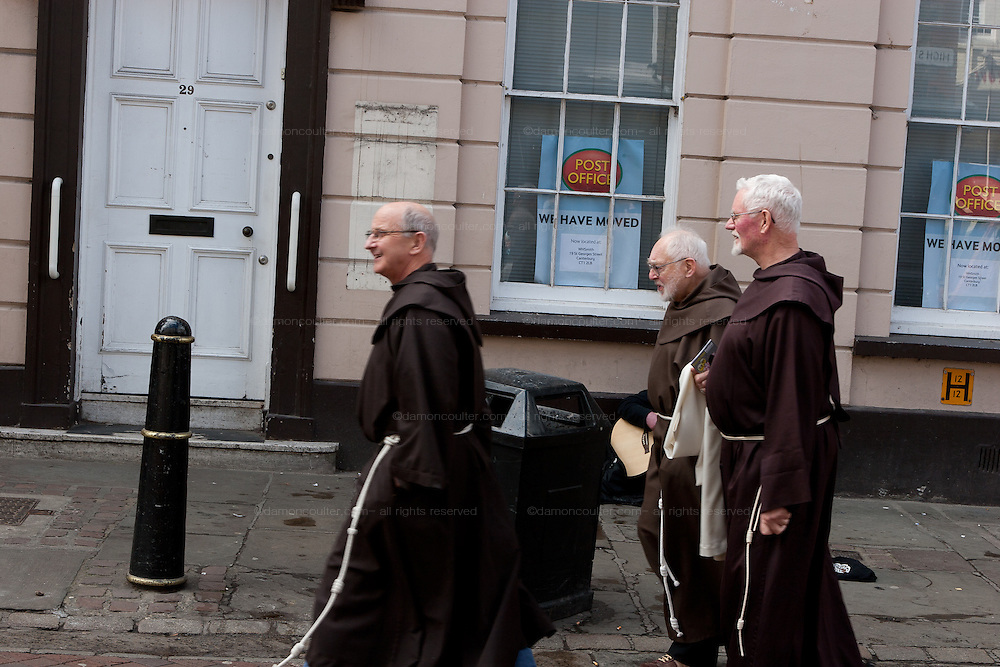 Christian Monks in front of a closed down post office, Canterbury Kent. England, UK April 11th 2008