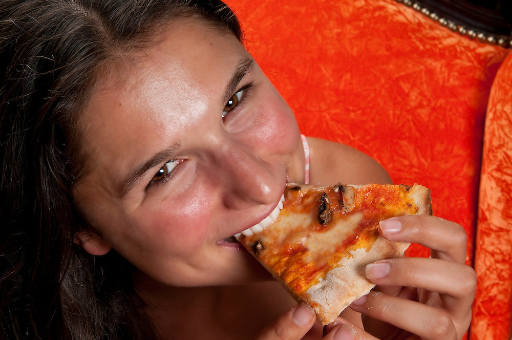 Young woman very happy eating a slice of pizza.
