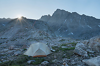 Morning sun spreading its rays over backcountry camp in Indian Basin, Harrower Peak is in the distance, Bridger Wilderness,  Wind River Range Wyoming