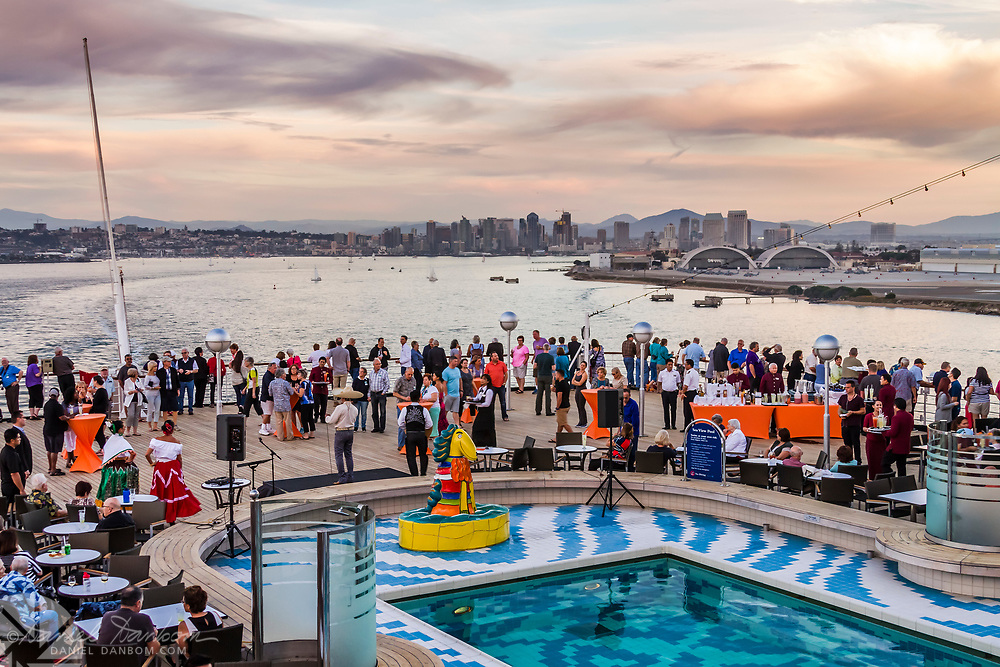 Sailing away from San Diego, on a cruise ship with view of the city skyline, and on deck party.