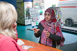 Woman asking for information at an enquiries desk,
