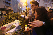 """Eliahoo Rouas Cohen and Esther Bekerman light a candle and say prayers for Meryl Bekerman, a hostage who was wounded in the Kosher supermarket<br /><br />French and Jews come together to make a vigil outside a Kosher supermarket in Porte Vincennes, Paris, France. Yesterday this Kosher supermarket was the scene of a hostage taking and followed by an armed shoot out between Jihadist gunmen and French police. It ended in a shoot out and with the death of the terrorists. Some hostages were killed and police injured.<br /><br />This event was directly linked to the attack on the offices of Charlie Hebdo, killing twelve people, including the editor and celebrated cartoonists two days before. This week was the deadliest week of terror attacks in France for over fifty years. Charlie Hebdo is a satirical publication well known for its political cartoons. <br /><br />As a solidarity actions with the deaths at Charlie Hebdo many placards read """"Je suis Charlie"""" translating as """"I am Charlie (Hebdo)"""". Demonstrators held aloft pens, brushes and crayons, symbolizing the profession of journalists and cartoonists who were killed."""