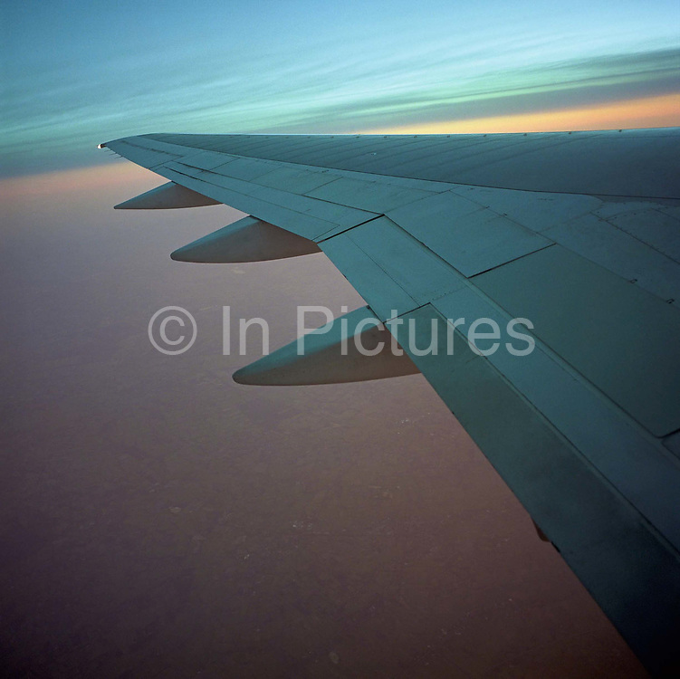In mid-flight between Hamburg in Germany and London Heathrow, we see a passenger's view of a climbing airliner's port wing and the hazy German landscape below at a high altitude. The sky above reflects its soft blue hue on the upper surface of the left wing but the air below is a soft pink, a rural patchwork of fields and villages. As an example of aerodynamic design, the flying machine is a perfect gesture towards the conquest of flight, copied from the characteristics of a bird's anatomy. As art, the mere beauty of taking to the air and maintaining level, organised speed is so routine, we rarely look our from our window to marvel at how and why. Picture from the 'Plane Pictures' project, a celebration of aviation aesthetics and flying culture, 100 years after the Wright brothers first 12 seconds/120 feet powered flight at Kitty Hawk,1903.