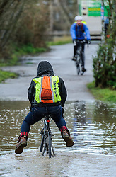 © Licensed to London News Pictures. 03/03/2014. BRISTOL, UK A woman makes her way with a bike through a flooded section of the cycle path and harbour railway line by the river Avon and Cumberland Road in Bristol during this morning's high tide. Photo credit : Artur Lesniak/LNP