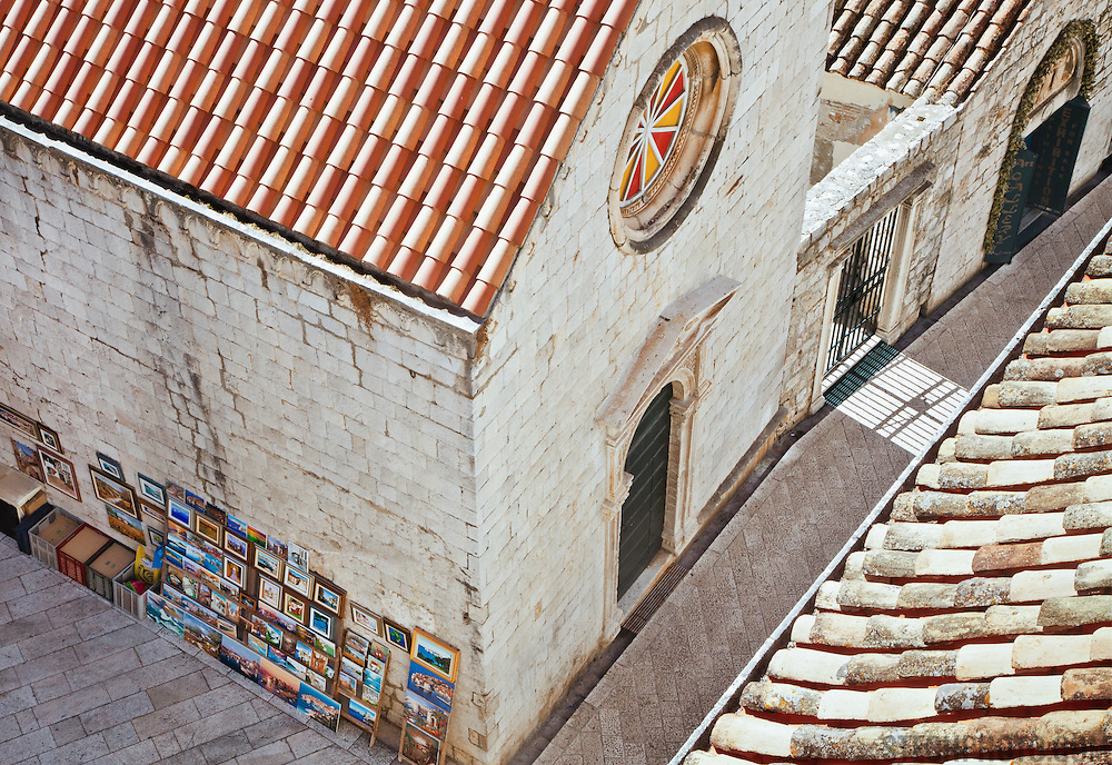 """A view from above of a street, buildings and art for sale in the old city of Dubrovnik, Croatia. <br /> <br /> Dubrovnik serves as the official setting of """"King's Landing"""" from the popular TV show """"Game of Thrones""""."""