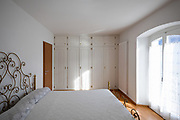 Master bedroom with doilies cover and large white wardrobe