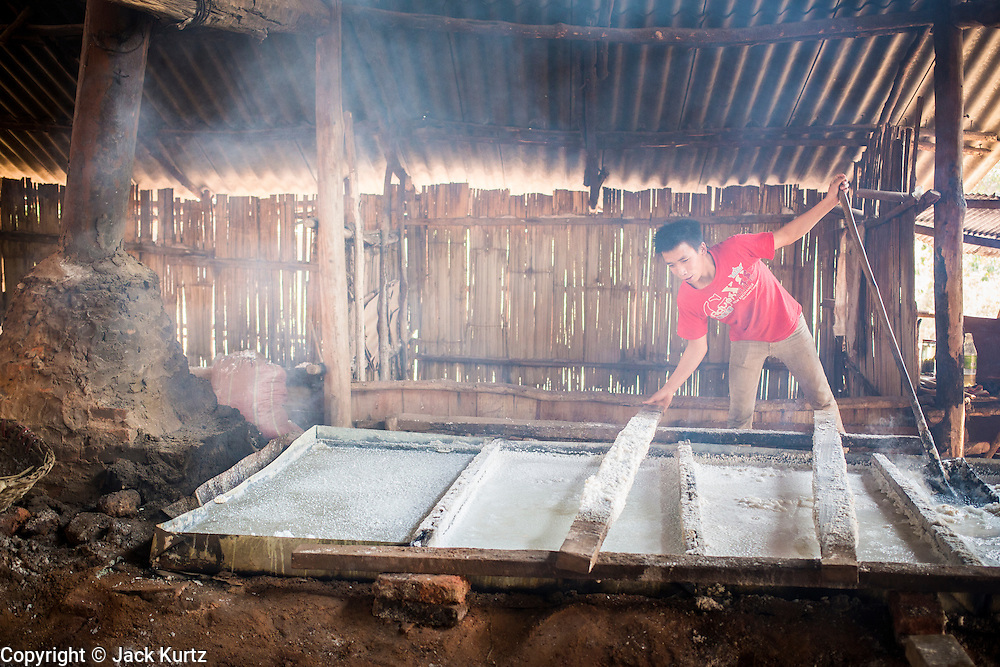 13 MARCH 2013 - BOTEN, LUANG NAMTHA, LAOS:  A worker checks a tray of boiling brine in a salt workshop in Boten, Laos. Salt in Boten is made by boiling briny water and collecting the salt that is left behind. The salt wells in Boten, Laos, just south of the Chinese border, have brought a measure of fame to the area for centuries. French forces asserted French dominance over the region in 1894 to control the salt trade. Some of the salt works face an uncertain future because of economic development from China. The area is being developed into a huge parking lot to accommodate truck and tourist traffic into and out of China.   PHOTO BY JACK KURTZ