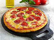 Pizza topped with Pepperoni, cheese, chilli & basil photo. Funky Stock pizzas photos