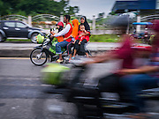 08 JULY 2013 - PATTANI, PATTANI, THAILAND:  A Thai Muslim family rides home from a grocery store Monday, the day before Ramadan. Ramadan starts July 9 and Monday was the last day observant Muslims were able to eat and drink during daylight hours. Muslims fast during the holy month of Ramadan, taking breakfast before dawn and not eating again until after sunset. The restaurants in Pattani, a Muslim majority city in southern Thailand, were packed Monday afternoon and evening.   PHOTO BY JACK KURTZ