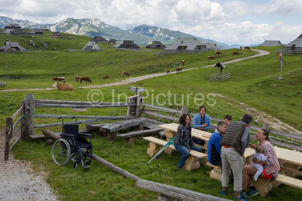 Walkers visiting the collection of Slovenian herders mountain huts in Velika Planina, on 26th June 2018, in Velika Planina, near Kamnik, Slovenia. Velika Planina is a mountain plateau in the Kamnik–Savinja Alps - a 5.8 square kilometres area 1,500 metres 4,900 feet above sea level. Otherwise known as The Big Pasture Plateau, Velika Planina is a winter skiing destination and hiking route in summer. The herders huts became popular in the early 1930s as holiday cabins known as bajtarstvo but these were were destroyed by the Germans during WW2 and rebuilt right afterwards by Vlasto Kopac in the summer of 1945.