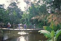 Gente cruzando un rio por un puente colgante en la selva, Cerro Delgado Chalbaud, Amazonas, Venezuela.