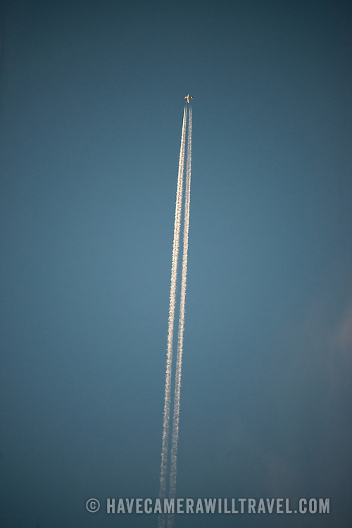 The distinct contrails of a plane flying overhead catch the last rays of the setting sun against a darkening clear sky.
