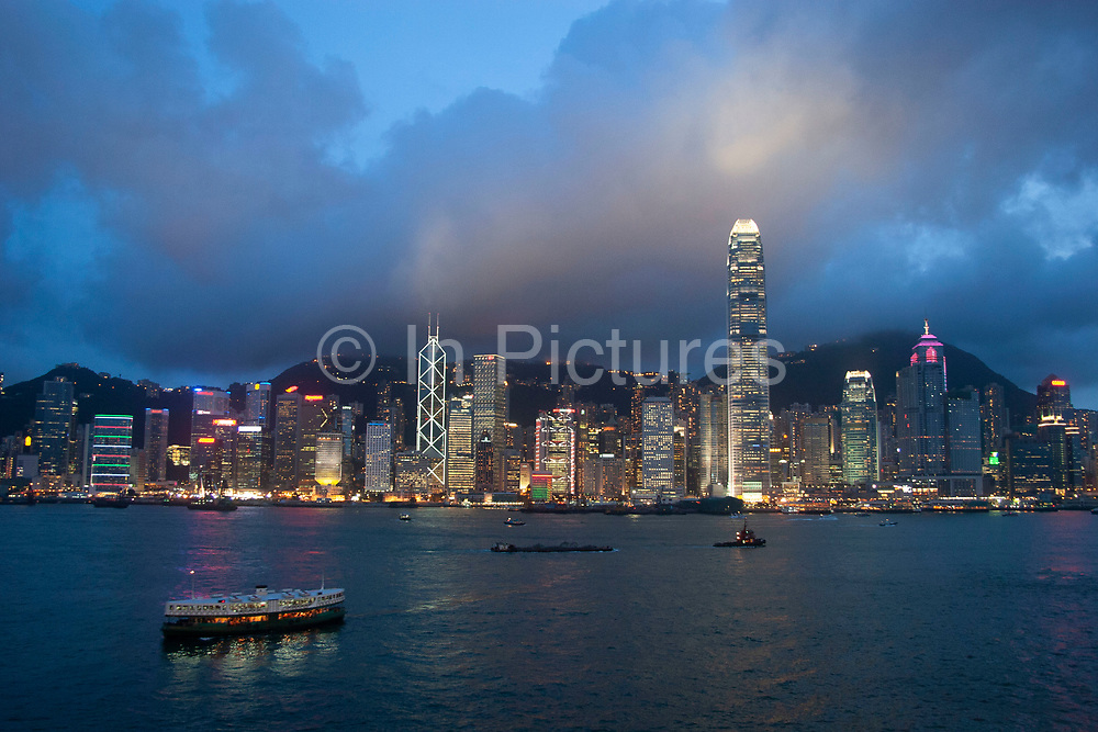 Clouds form over the peak at sunset and collect over the Hong Kong dramatic night skyline as the Star Ferry crosses the harbour in Hong Kong, China. Many of Hong Kong's distinctive buildings line up including the once dominant Bank of China building. Two International Finance Centre now towers over the skyline at 88 stories 415m tall, lighting up the clouds it nearly reaches. Below in the water a Star Ferry crosses from the main terminal at Tsim Sha Sui in Kowloon to Central.