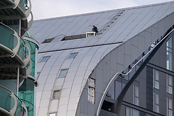© Licensed to London News Pictures. 25/05/2021. London, UK. A building maintenance worker sits on a platform during an inspection after a large section of cladding (botton of frame) on the Arc Tower in Ealing came loose. Emergency services were forced to close a section of Uxbridge Road while the building was made safe. Photo credit: Peter Manning/LNP