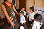 Young Nepalese children hold hands in a circle with a children's activity facilitator during a relationship building session facilitated by a staff member called Sandi in the Voice of Children centre in Kankeshori area of Kathmandu, Nepal.  The not-for-profit organisation supports street children and those who are at risk of sexual abuse through educational and vocational training opportunities, health services and psychosocial counseling.  These young children have recently been found by the charity and attend the children's drop-in centre where they play games and activities.