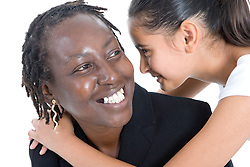 Young girl whispering into an older woman's ear,