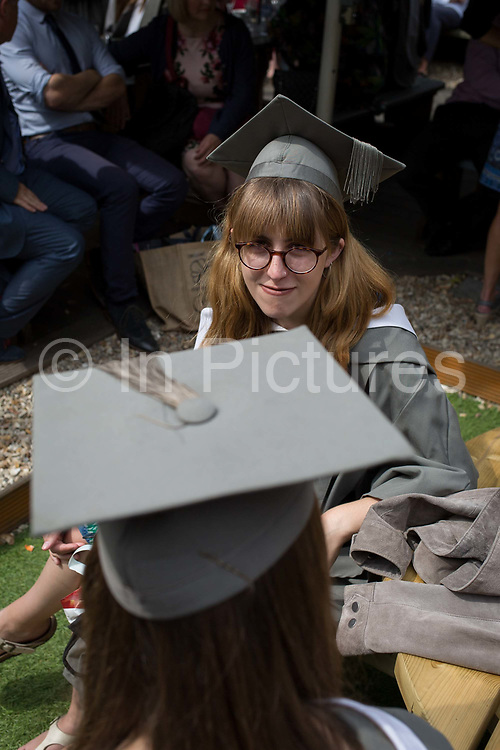 Young graduates wearing rented gowns and mortarboards at a private party before their university graduation ceremony, on 13th July 2017, at the University of York, England.