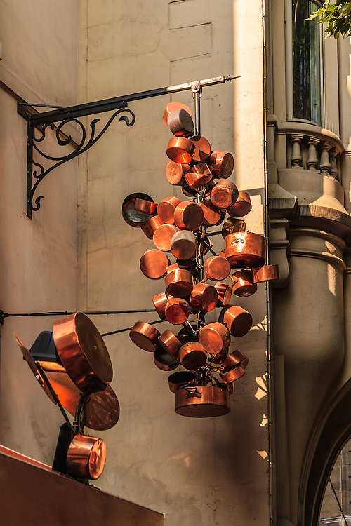 Pots and pans hang above restaurant entrance in Paris, France. Paris is the gourmet capital of the wolrd.