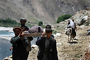 Relatives and volunteers carry the dead body of Qamar, a 26-year-old tuberculosis patient who died of complications two weeks after the delivery, to her village as her mother-in-law carries the baby on a donkey in Shohada district in Badakshan province, Afghanistan, Monday, May 21, 2007.