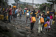 Children go up and down the lava-filled hill carrying water containers in Himbi neighborhood of Goma.