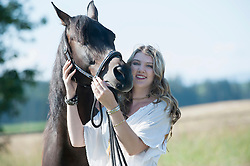 Young woman stroking her brown horse standing on meadow and smiling, Bavaria, Germany