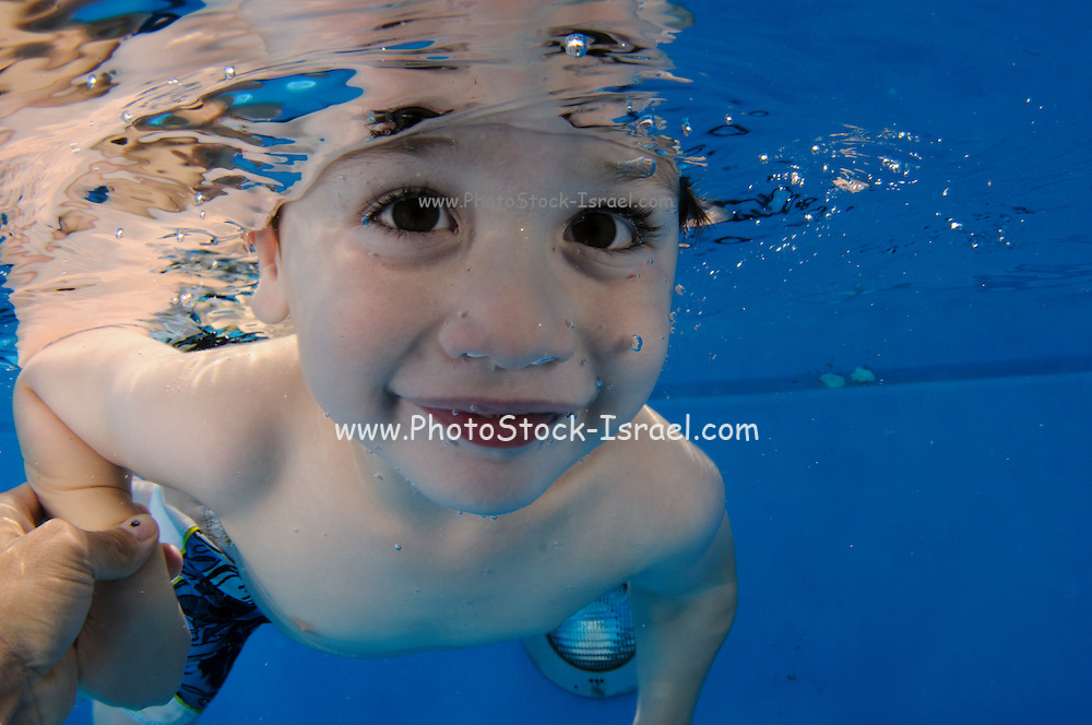 Young boy holds her breath while floating underwater