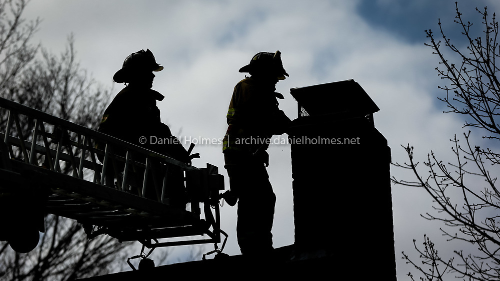(4/24/15, HOLLISTON, MA) Holliston firefighters Matt Dellicker, right, and Rich Couglin work to extinguish a chimney fire that started around 9:30 a.m. at 135 Norfolk St. in Holliston on Friday. Deputy Fire Chief Moore said there was no damage to the house, which was built circa 1757. Daily News and Wicked Local Photo/Dan Holmes