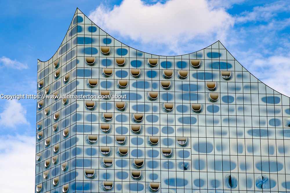 View of abstract glass facade new Elbphilharmonie concert hall nearing completion on River Elbe in Hamburg Germany