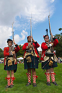Old Westbury, New York, U.S. - August 23, 2014 - L-R, TIM NORTON, of CT, AARON BOATRIGHT, of CT, and CONRAD BENDER IV, of NJ, are American Revolution re-enactors portraying members of the 42nd Royal Regiment of Foote, at the 54th Annual Long Island Scottish Festival and Highland Games, co-hosted by L. I. Scottish Clan MacDuff, at Old Westbury Gardens. The regiment, The Black Watch, was raised in the Scottish Highlands in 1740 and fought for the British.