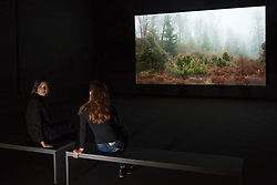 """© Licensed to London News Pictures. 24/09/2018. LONDON, UK. Staff members sit next to a work called """"BRIDGIT"""" showing iPhone recordings of the Scottish countryside.  Preview of an exhibition unveiling the four artists shortlisted for Turner Prize 2018 at Tate Britain. The exhibition is open 26 September to 6 January 2019.  Photo credit: Stephen Chung/LNP"""