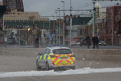 "© Licensed to London News Pictures . 10/12/2014 . Blackpool , UK . A police car is sprayed with foam from the sea on Blackpool Promenade . An explosive cyclogenesis - a fast developing storm in which air pressure falls rapidly - known as a "" weather bomb "" - hits the North of England , bringing storms to the region . Photo credit : Joel Goodman/LNP"