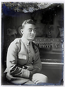 vintage portrait of soldier sitting by a piano on deteriorating glass plate