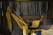Yellow tractor stored undercover in a smallholding shed during spring beofre another year's usage.