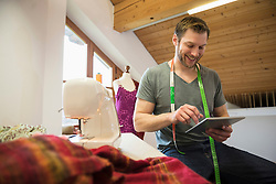 Male dressmaker working on digital tablet with sewing machine, Bavaria, Germany