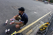 Manager of Horizon Fitness womens' road racing cycling team prepares drinks bottles for his cyclists in Woking.