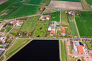 Nederland, Groningen, Oldambt, 01-05-2013; boerderijen in Oostwold, aan de oevers van het Oldambtmeer, onderdeel van Blauwestad. Het meer dienst voor recreatie en waterberging.<br /> Het project Blauwe Stad was oorspronkelijk bedoeld om de economisch achtergebleven regio van Noordoost Groningen een impuls te geven. De economische en huizen crisis gooit echter roet in het eten.<br /> Old farms on the edge of the new recreational Oldambt lake, part of Blauwestad (Blue City), the newly constructed residential area. The Oldambt lake also serves as water storage. The Blue City project is meant to give a boost to the  economically backward region of northeast Groningen, but the financial crisis has slowed down real estate developments.<br /> luchtfoto (toeslag); aerial photo (additional fee required);<br /> foto Siebe Swart / photo Siebe Swart1